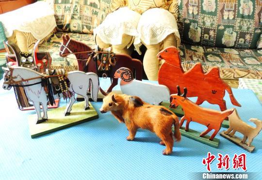 中新网博湖9月22日电 (王陆斌东华)在新疆巴州博湖县,一名7旬蒙古族非遗手艺人阿拉布吉退休后,花了15年时间同老伴一起制作民族手工艺品400余件,用巧手保存民族文化。9月21日,记者走进这对老夫妻家中一探究竟。   在两位老人的家中,满屋子的民族手工艺品让记者眼花缭乱,墙上挂的有民用的马皮带、缰绳、马嚼子和马鞭子等民族手工艺饰品,同时展示柜上分别摆有木马、木牛、蒙古包等小型木饰品。   阿拉布吉老人告诉记者,这些都是他和老伴做的,自己从8岁时跟着爷爷学到了手艺,老伴巴依尔也是位优秀的民间艺人,196