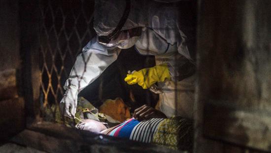 图为医生在疑似埃博拉患者身上采取样本。