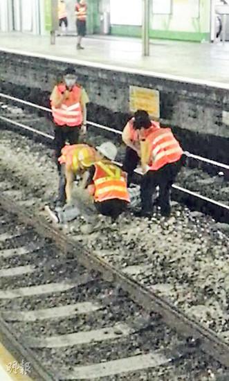 5名港铁职员在铁轨上,将一名不断叫嚷的中年汉合力抬起,送返月台。香港《明报》图