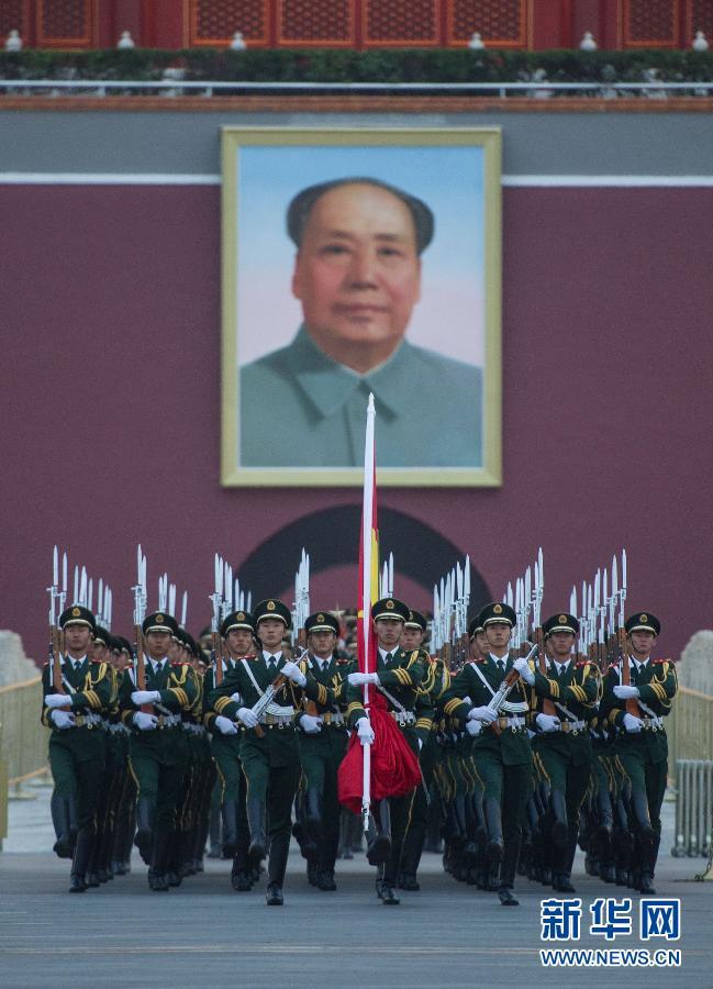 10月1日,国旗护卫队战士护送国旗走向天安门广场。当日清晨,来自全国各地的约12万名群众在北京天安门广场观看升国旗仪式,庆祝中华人民共和国成立65周年。 新华社记者 罗晓光 摄