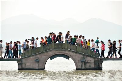 昨日,游客在杭州西湖景区游览。新华社发