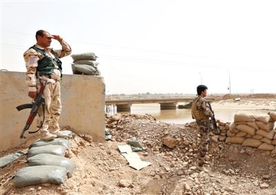 """9月29日,伊拉克,库尔德武装人员手持武器在面向""""伊斯兰国""""极端组织阵地的前线守卫。"""