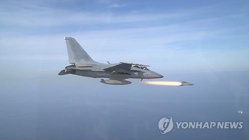 """韩国自主研制的FA-50战斗机8日在韩半岛东部海域上空首次进行空对地导弹""""AGM-65G""""实弹射击训练。(韩联社)"""