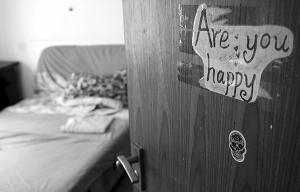 """在郭宜品住的出租屋房门上,贴有""""Are you happy""""字样"""