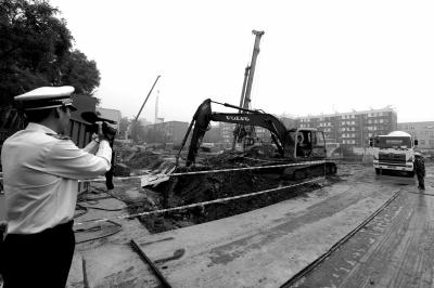 学院南路一科研楼项目有3台挖掘机违规进行土方作业,被城管队员当场责令停工。京华时报记者欧阳晓菲摄