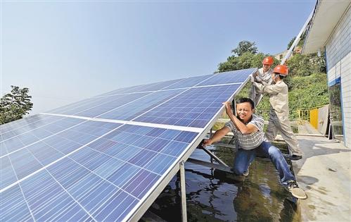 10月9日,彭小平正在和电力工人一起安装光伏发电板。记者 白麟 摄