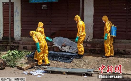 资料图:当地时间2014年10月8日,塞拉利昂弗里敦,卫生工作者正从街头一具疑似因感染埃博拉病毒而死亡的尸体上收集样本。塞拉利昂的埋尸队本周进行了罢工,将尸体抛在该国首都的街头。