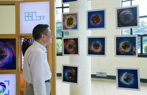 参观者欣赏摄影师余儒文的获奖作品