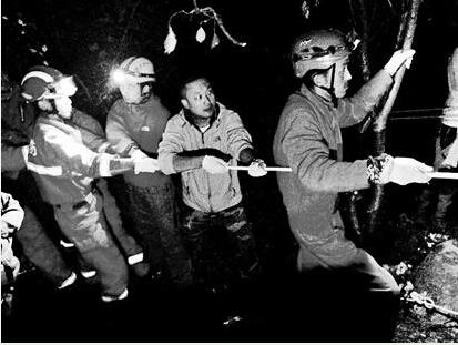 图为:救援人员将钱继伟的遗体拉出天坑