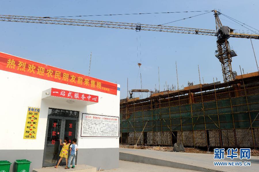 """10月14日,在安徽省阜南县许堂乡,农民刘富森在展示在路边晾晒玉米时从土里""""淘""""出来的玉米。"""