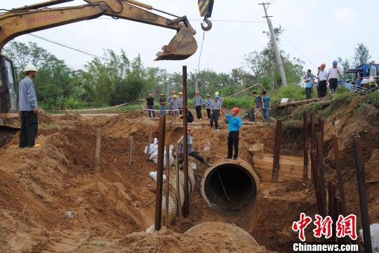 挖掘机正在清理管道作业面。 王辛莉 摄