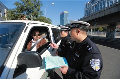 昨日,岳各庄桥南,交警在对过往的司机进行系安全带的宣传。新京报记者 浦峰 摄