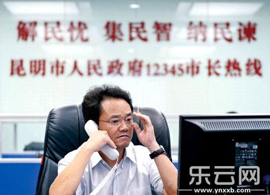 """2014年7月31日下午,常务副市长李喜坐镇""""12345""""市长热线办公室,接听市民来电并回复网友的提问。本报记者 杨映波 摄"""