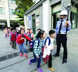 保安手拿钢叉站在学校门口护卫学生