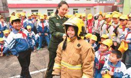 10月31日,学生在消防官兵帮助下试穿战斗服。当日,太师三附小200余名学生走进太原消防支队特勤一中队,通过互动式参观学习,提升消防安全意识和自防自救能力。