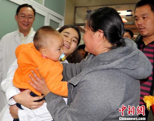 """11月5日,在医护人员的精心照料下,来自山东的""""扎针女婴""""术后恢复良好,回到母亲怀抱。 杨建军 摄"""