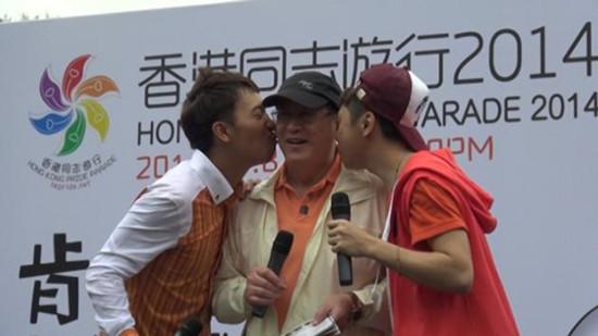 香港平等机会委员会主席周一岳(中)出席活动,获主持人献吻。香港《明报》