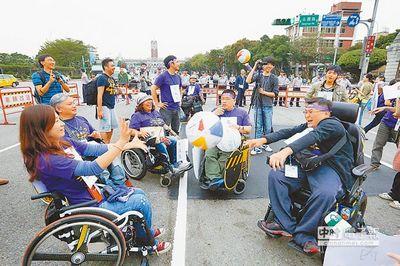身心障碍大游行11月8日举行,轮椅族上演传接球行动剧,讽刺台当局晋用他们时,只会互相踢皮球。(来源 台湾《中国时报》)