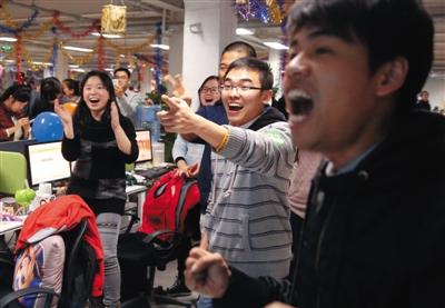 """11月11日凌晨0点01分,""""双十一""""促销刚开始一分钟,位于通州的某服装公司总部内,部分员工看着不断攀升的销售额,发出欢呼。新京报记者 李冬 摄"""