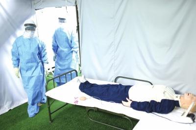 """302医院数字化模拟培训中心,队员们在高温下穿着3层防护服巡视""""病房""""。"""