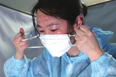 队员摘下口罩和护目镜,脸上布满了汗水和皮筋勒出的红印。