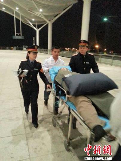 客运员和急救人员一起护送患者。 董伟 摄