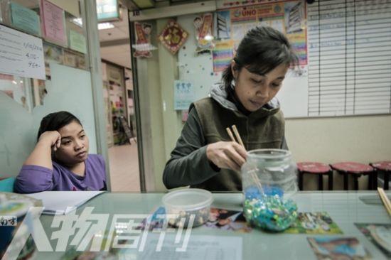 一位菲佣在女佣中介里练习使用筷子(图/郭浩忠)