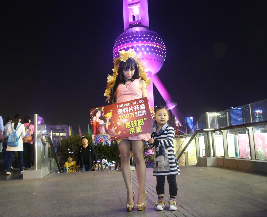 火辣美女上海闹市扮摇钱树求摇 围观者多无人