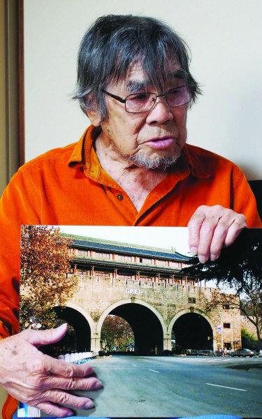 原文配图:2007年12月,南京大屠杀发生70周年之际,三谷翔重返南京,在挹江门前留影,并向南京人民道歉。图为他向记者展示照片。