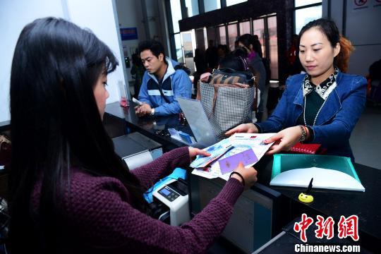 """一名乘客正拿着台币在票务中心准备购买""""海峡号""""船票。 蔡起辉 摄"""