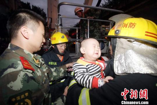 消防官兵在火灾现场营救、疏散被困群众。 容肖 摄