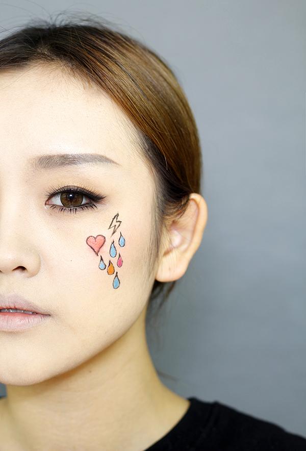 再用彩色眼线笔在脸部画出可爱的图案.