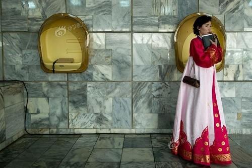 朝鲜平壤,一名穿传统服装的妇女在羊角岛国际酒店里用手机通话。