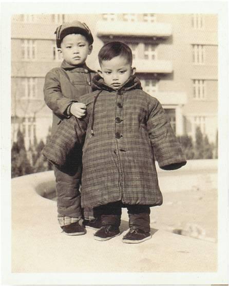 三岁的莫华伦(右)和哥哥(左) 摄于北京  小小的莫华伦虽然低头沉思状,却掩不住那双动人的大眼睛闪烁出迷人的艺术气质。略大的连帽格子棉衣虽然极可能是哥哥的旧衣,样式在今天看来依旧时髦。修剪得整齐帅气的小分头,足见母亲对儿子的深爱和照顾。