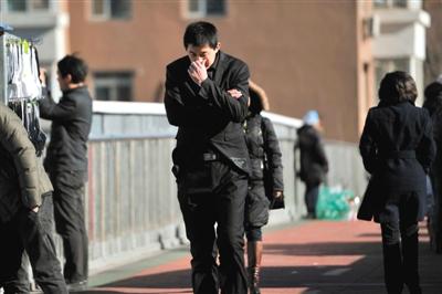 12月1日,北风呼啸,一名男子走在街头,刺骨的寒风让他赶忙裹紧外衣。图/东方IC