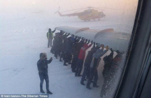 俄罗斯一架客机起落架结冰无法起飞,全机74名乘客和7名机组人员下机,在摄氏零下52度下以人手推动飞机。(网页截图)