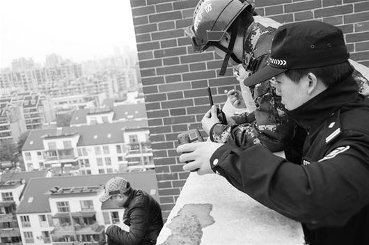 图为:男子坐在11楼顶外墙屋檐上,双腿悬在空中