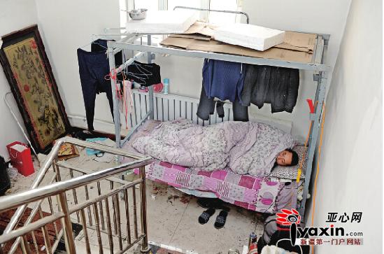 12月3日,七道湾创业园内一处4层的办公楼里,一名住在冰冷楼道里的工人躺在被窝里等待着拖欠了两年的工钱。亚心网记者 张万德 摄