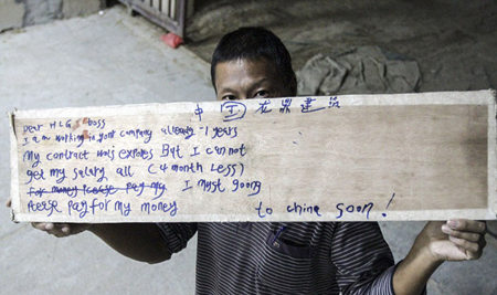 一名在迪拜的中国工人举标语求助讨薪。(网页截图)