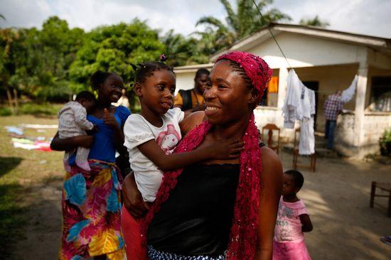一名管理员正怀抱婴儿赛库,当天晚些时候,赛库将回到自己的大家庭。