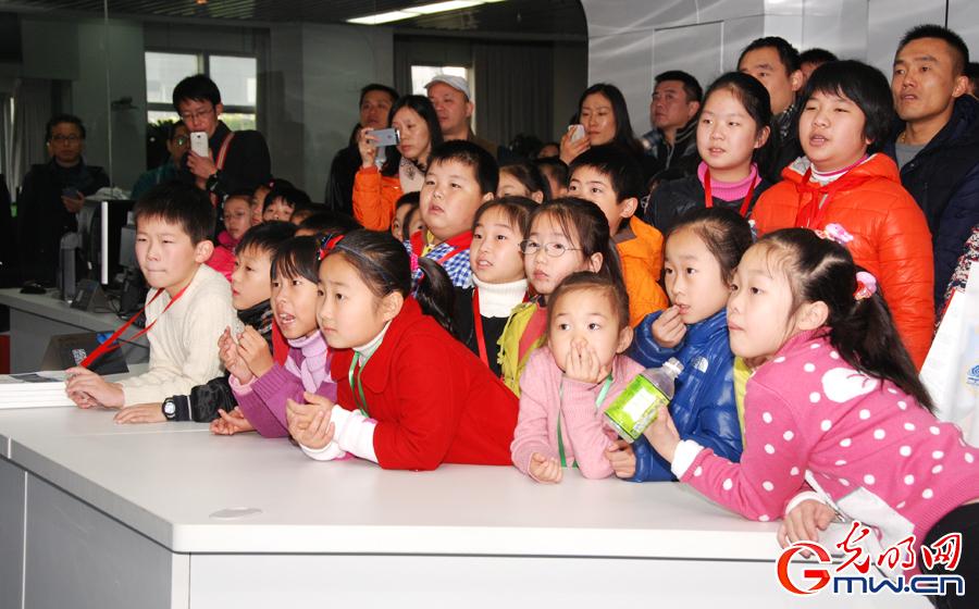 陪同孩子参观的家长正在虚拟气象播报厅外,用手机录制孩子的天气预报节目(光明图片
