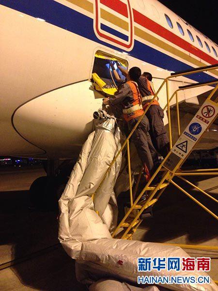 图为机务人员正在更换充气滑梯。李鹏程