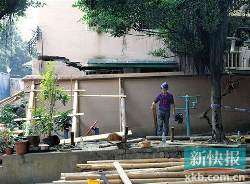 昨天,抢修工人用木头撑持开裂歪斜的墙体,以避免其接续下陷。 新快报记者 毕志毅/摄