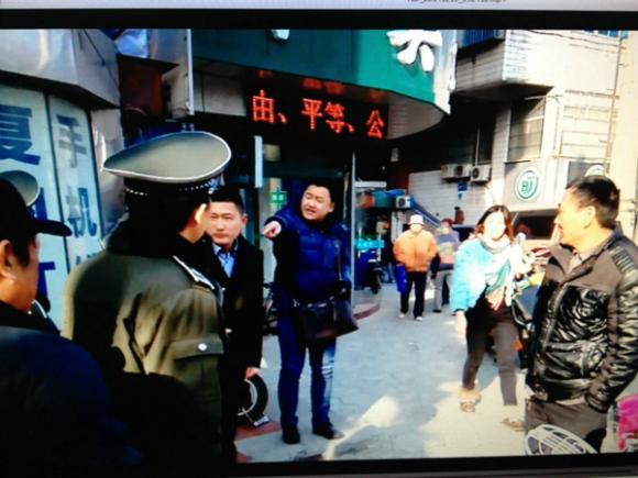 砍人男子(穿蓝色衣服背包者)因发传单遭阻止与城管队员争执。图片来自城管执法记录仪截屏