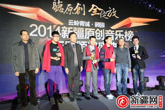 2014年年度最佳作词《新疆美食》词作者何方、2014年年度最佳作曲《亲爱的乌鲁木齐》曲作者陈健、2014年年度最佳唱作人乔晨领奖。(记者宁松摄)