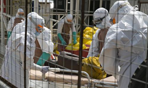 医务工作者在塞拉利昂的埃博拉治疗中心中看护病人。