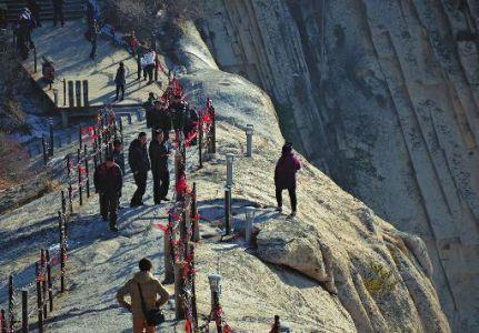 着口罩,独自一人站在护栏外悬崖边,十分危险.在护栏内,有男子面