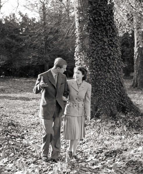 1947年11月,伊丽莎白二世(右)和菲利普亲王在英国南部汉普郡的布罗德兰兹庄园度蜜月时携手散步。