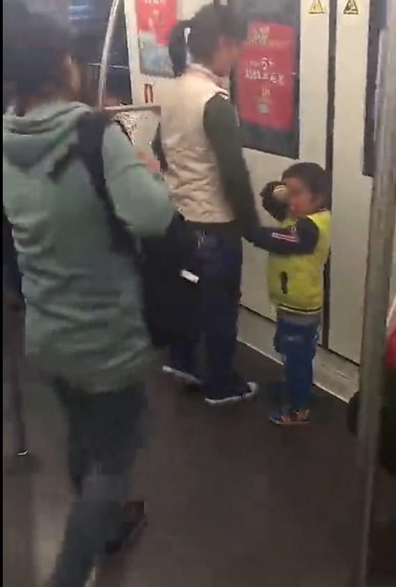 视频中,行乞女子带着小孩走到车门处。