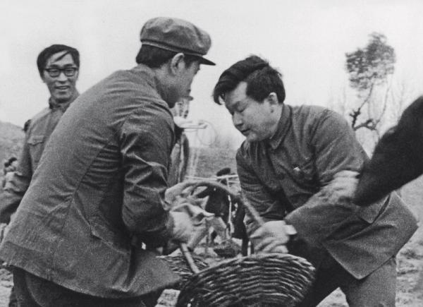 《辽沈大地改革潮》书内收录的珍贵旧照。图为1985年8月27日,李长春与群众一起抢修辽河大堤。 人民网 图